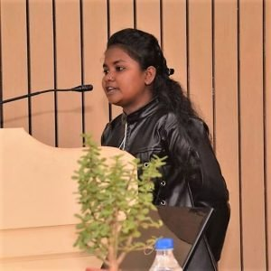 A girl in a black jacket standing at a podium and speaking into a mic. She has long hair that are tied at the back. There is also a plant visible in the photograph.