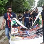 """Some young men and women are walking. Some of them are holding a banner saying """"IDIA Jharkhand: A Walk to Awaken"""". There is IDIA logo on the banner."""